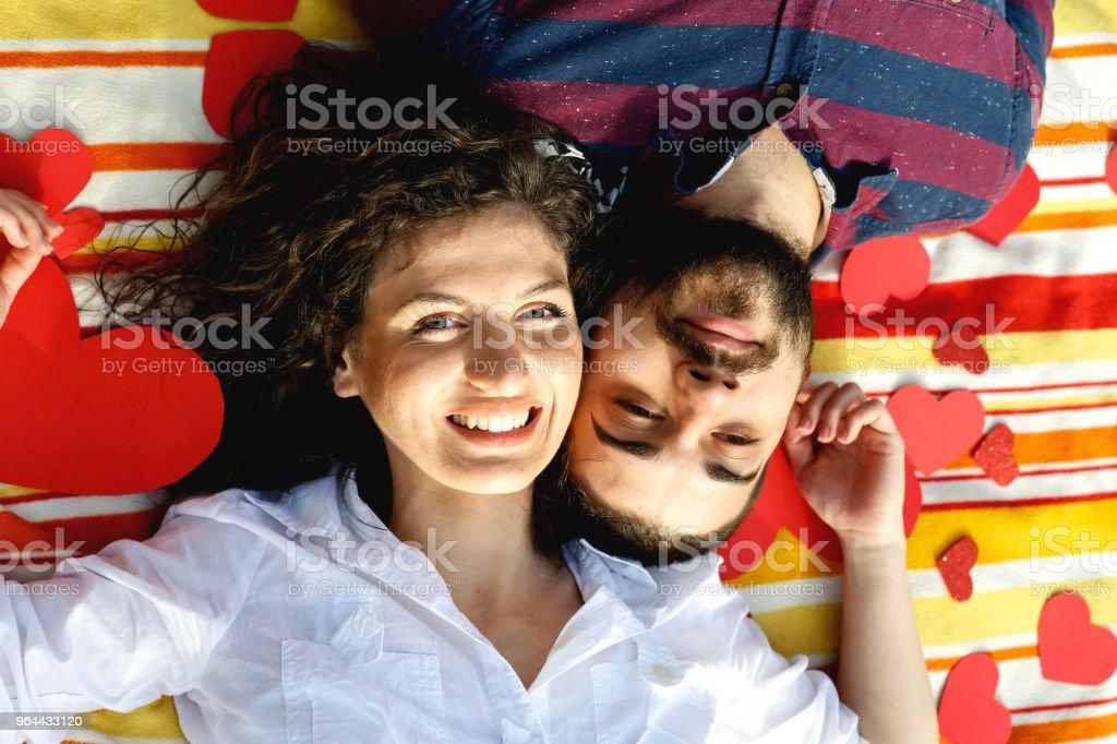 Vista superior do feliz casal jovem sorrindo enquanto deitado no cobertor com corações - Foto de stock de A Data royalty-free