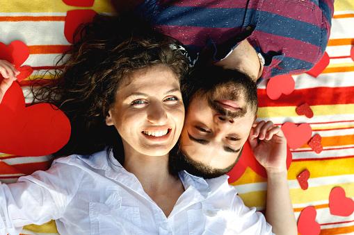 Foto de Vista Superior Do Feliz Casal Jovem Sorrindo Enquanto Deitado No Cobertor Com Corações e mais fotos de stock de A Data