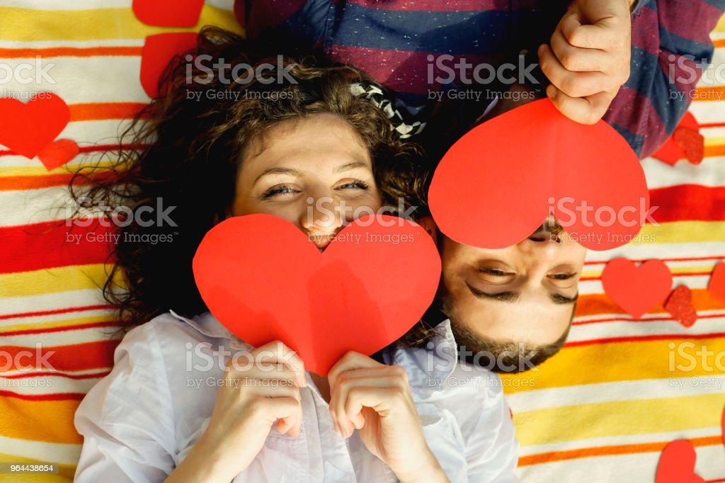 Top view of happy young couple smiling while lying on blanket with hearts - Royalty-free Adult Stock Photo