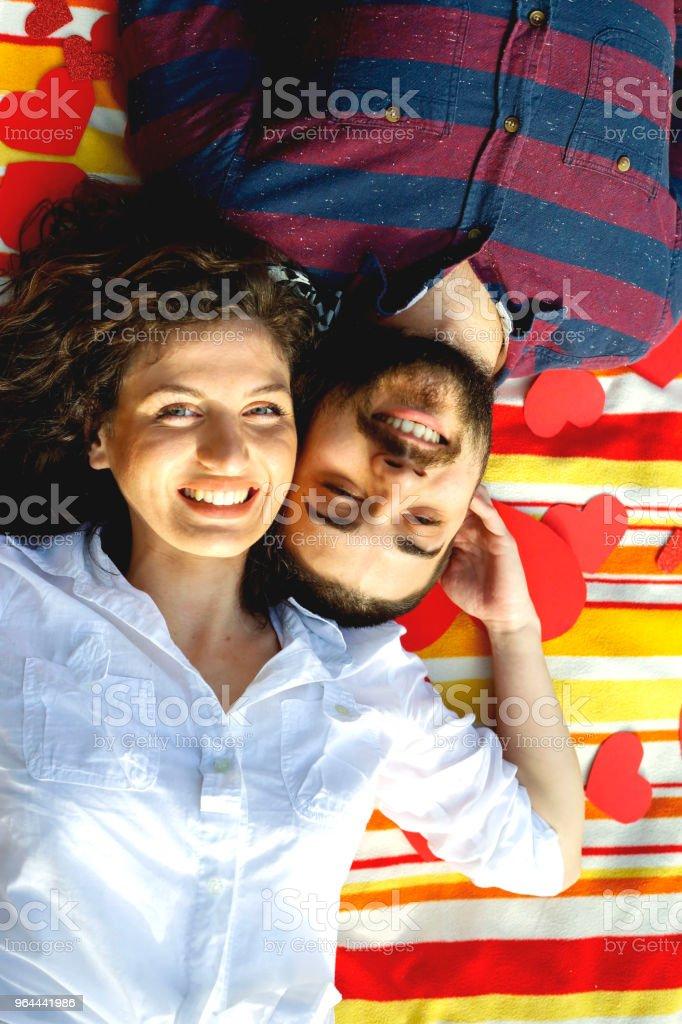 Vista superior do feliz casal jovem sorrindo enquanto deitado no cobertor com corações - Foto de stock de Adulto royalty-free
