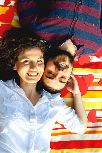 Foto de Vista Superior Do Feliz Casal Jovem Sorrindo Enquanto Deitado No Cobertor Com Corações e mais fotos de stock de Adulto