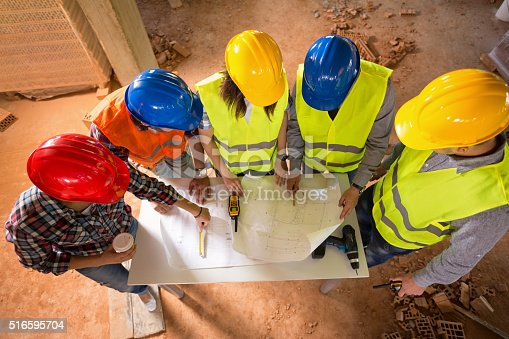 516607254istockphoto Top view of hard hats of architects at construction site 516595704