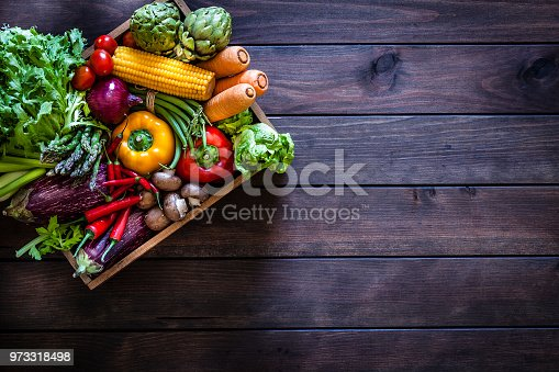 Top view of a wooden crate filled with fresh organic vegetables placed at the top-left of a dark wooden plank leaving useful copy space for text and/or logo at the right. Vegetables included in the composition are lettuce, tomatoes, corn, carrots, bell pepper, eggplant, asparagus, edible mushrooms, celery, artichoke and green beans. Low key DSRL studio photo taken with Canon EOS 5D Mk II and Canon EF 70-200mm f/2.8L IS II USM Telephoto Zoom Lens