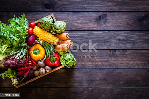 Top view of a wooden crate filled with fresh organic vegetables placed at the left of a dark wooden plank leaving useful copy space for text and/or logo at the right. Vegetables included in the composition are lettuce, tomatoes, corn, carrots, bell pepper, eggplant, asparagus, edible mushrooms, celery, artichoke and green beans. Low key DSRL studio photo taken with Canon EOS 5D Mk II and Canon EF 70-200mm f/2.8L IS II USM Telephoto Zoom Lens