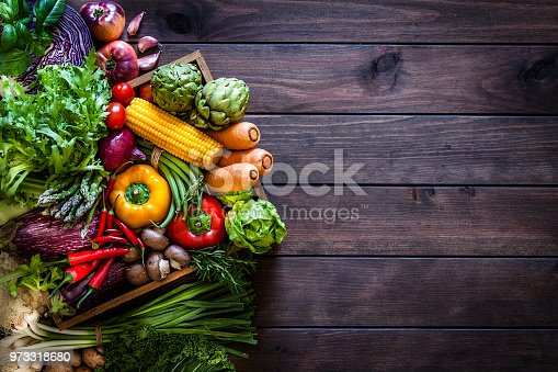 Top view of a wooden crate filled with fresh organic vegetables placed at the left of a dark wooden plank leaving useful copy space for text and/or logo at the right. Some vegetables are out of the crate. Vegetables included in the composition are lettuce, tomatoes, corn, carrots, bell pepper, eggplant, asparagus, edible mushrooms, celery, artichoke and green beans. Low key DSRL studio photo taken with Canon EOS 5D Mk II and Canon EF 70-200mm f/2.8L IS II USM Telephoto Zoom Lens