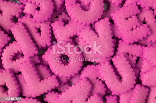 Top view of heap of vivid pink alphabet shaped biscuits spelling the word LOVE U