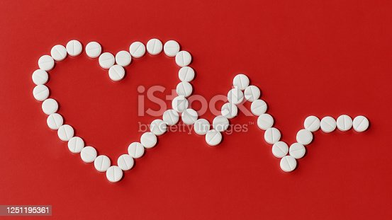 istock Top view of heart and cardiogram made of white pills over red background. Heart and cardiovascular disease, health and treatment concept 1251195361