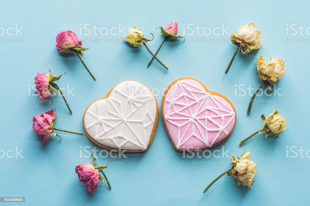 top view of heart shaped cookies and decorative flowers isolated on blue stock photo