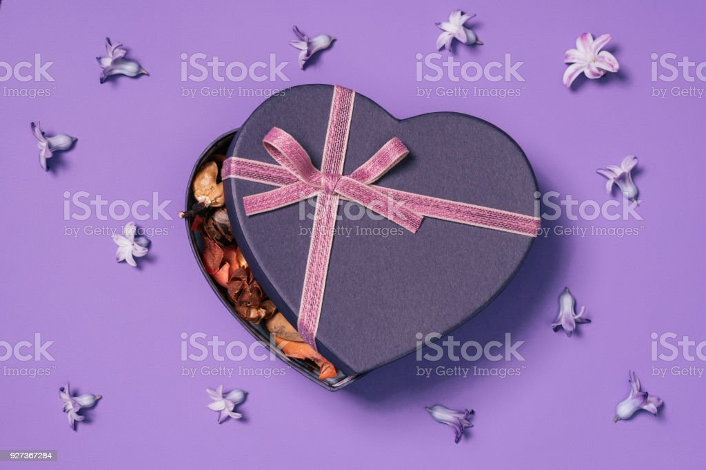 top view of heart shaped gift box with flowers around isolated on purple top view of heart shaped gift box with flowers around isolated on purple Arrangement Stock Photo