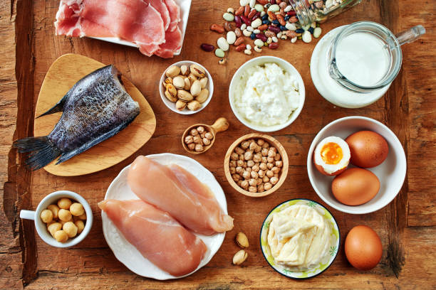 Top view of high-protein foods. Dairy, eggs, fish and meat, chickpea, beans and nuts on rustic wooden table. nut food stock pictures, royalty-free photos & images