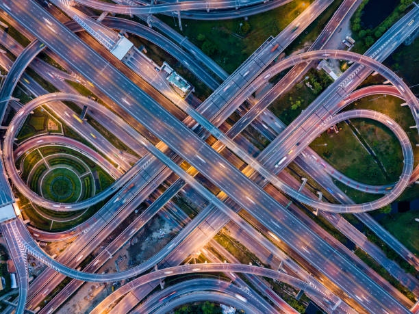 Top view of Highway road junctions at night. The Intersecting freeway road overpass the eastern outer ring road of Bangkok, Thailand. stock photo