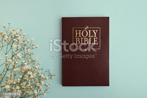 Top view of holy bible on round with flowers on green background