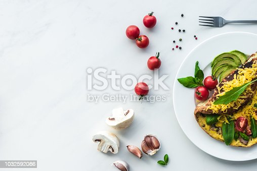 top view of homemade omelette with cherry tomatoes, avocado pieces and cutlery on white marble surface