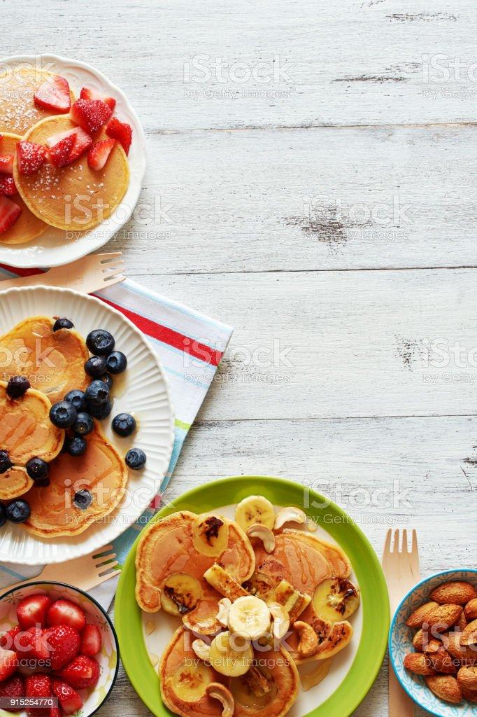 Draufsicht der hausgemachte Pfannkuchen mit Beeren, Banane, Nuss und Honig auf weißen Tisch mit Textfreiraum. – Foto