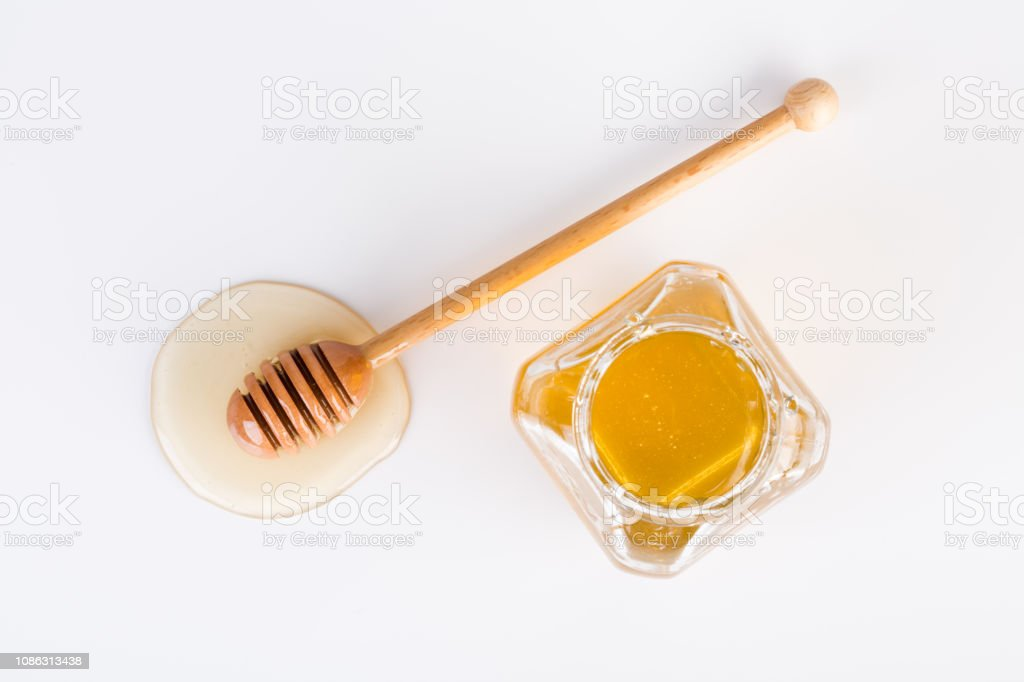 Top view of honey and honey dipper on white background stock photo