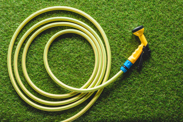 top view of hosepipe on grass, minimalistic conception - garden hose stock pictures, royalty-free photos & images