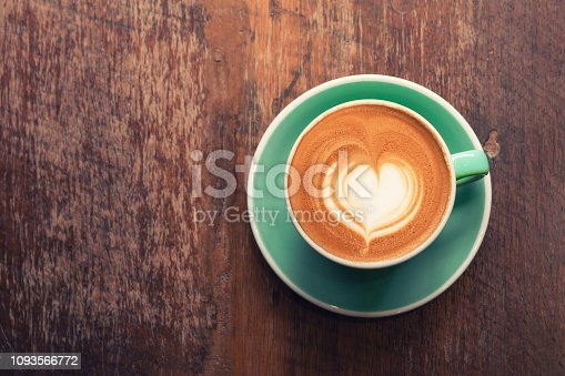 istock Top view of hot cappuccino coffee in a green cup with latte art and saucer on wooden table background. 1093566772