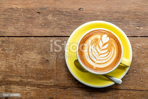 Top view of hot cappuccino coffee in a yellow cup with latte art and saucer on the wooden table background.
