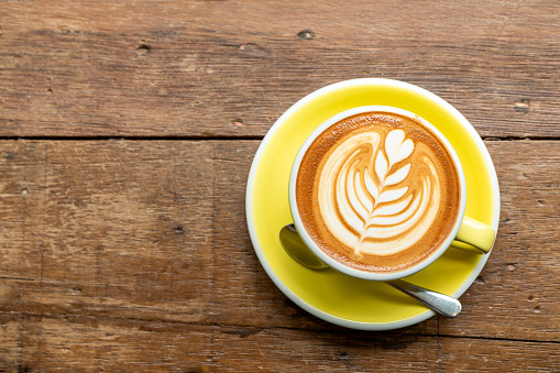 Top view of hot cappuccino coffee in a yellow cup with latte art on wooden table background.