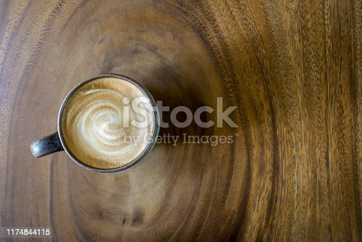 Top view of hot coffee cappuccino latte with stirred spiral milk foam in green ceramic cup on beautiful wood texture (annual ring) table background.