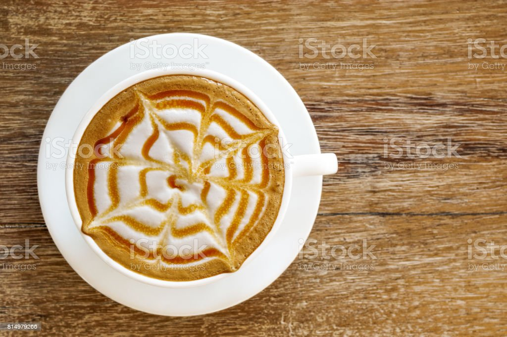 Top view of hot coffee caramel macchiato cup on wood table background. stock photo