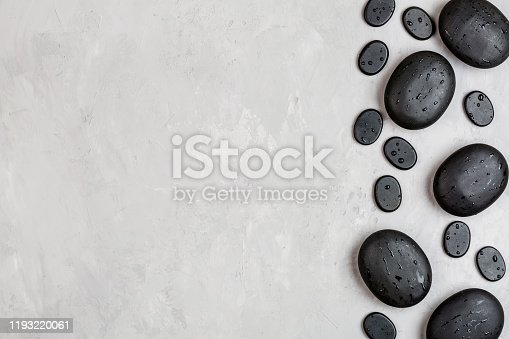 Top view of hot spa stones set for massage treatment on gray concrete background with copy space. Elegant and luxury spa. Flat lay, overhead, mockup, template. Health and beauty care concept