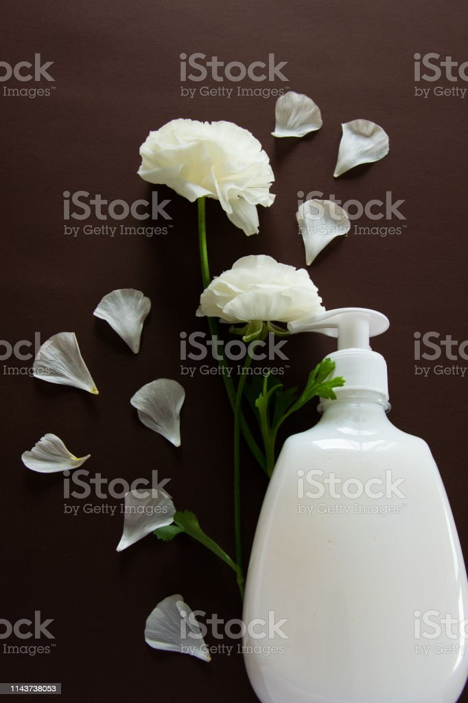 Top view of hygienic/cosmetic product and flowers on brown...