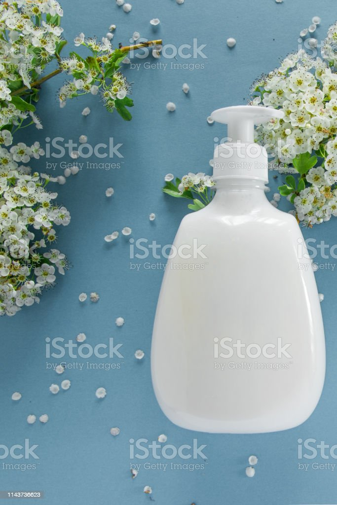 Top view of hygienic/cosmetic product and flowers on soft blue...