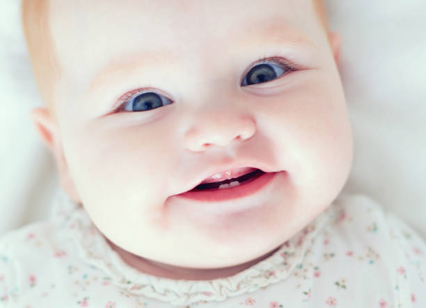 top view of infant baby girl, smiling with her first two teeth stock photo