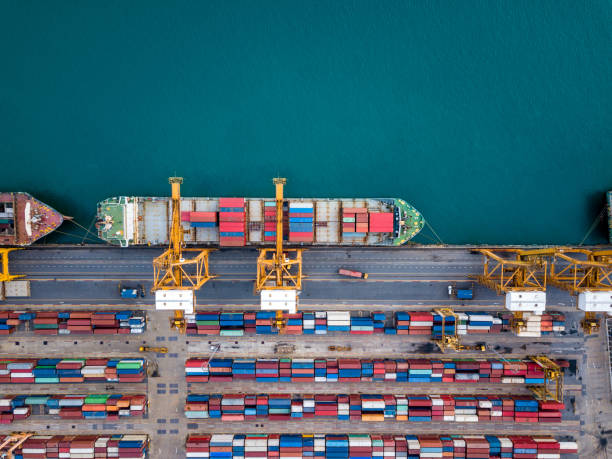 Top view of international port with Crane loading containers in import export business logistics. Top view of international port with Crane loading containers in import export business logistics. container ship stock pictures, royalty-free photos & images