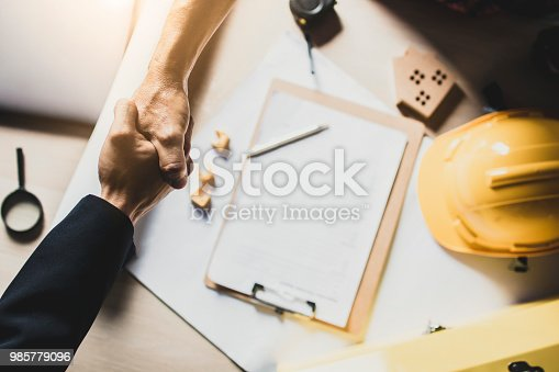 istock top view  of investor, businessman  shakes hand with engineer or architect on working table at construction site, after finishing  discussion and meeting 985779096