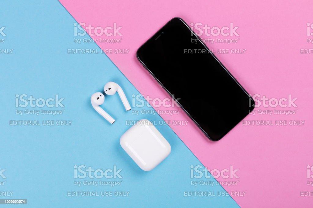 Bovenaanzicht van iphone XS en Apple AirPods op roze en blauwe achtergrond. - Royalty-free Aanmoediging Stockfoto