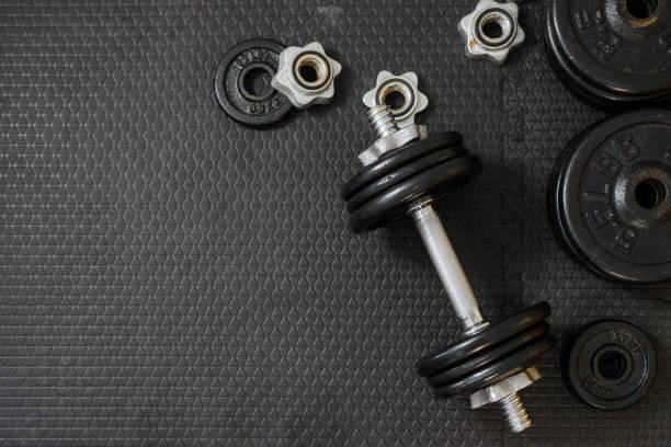 Oberansicht von Eisernen Hanteln oder Gewichten auf schwarzem Boden mit Kopierplatz für Text. Flache Laienzusammensetzung. Gesundheitskonzept. – Foto