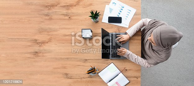 istock Top view of islamic woman working on laptop at workplace 1201215924