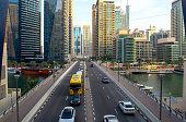 DubaiUAE - November 11, 2020: Top view of JBR Marina bridge with many cars and people. Jumeirah Beach Residence and Marina walk. Dubai road, street among beautiful towers and river.