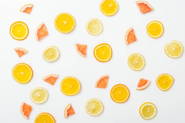 白い表面のジューシーカットフルーツのトップビュー - グレープフルーツ ストックフォトと画像
