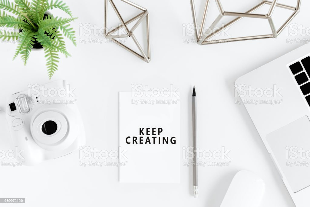 Top view of keep creating motivational quote and instant camera at workplace - Photo