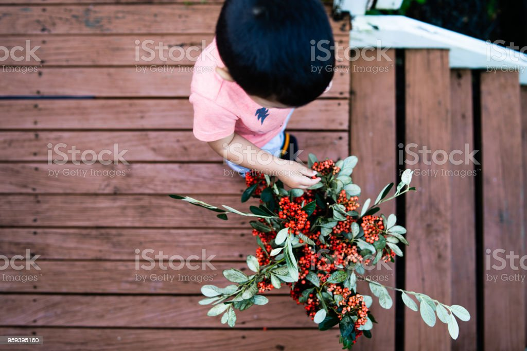 Top view of kid helping to put together bouquet. stock photo