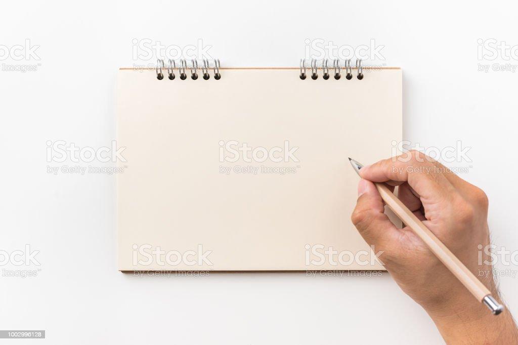 Vista superior de la página en blanco, cuaderno de espiral de kraft y mano del hombre con pluma de madera - foto de stock