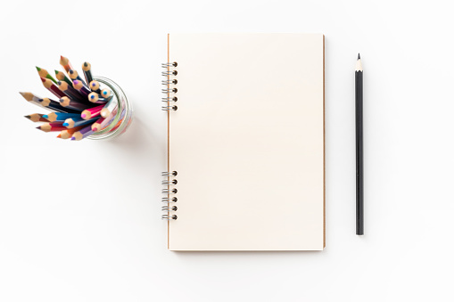 Design concept - Top view of kraft spiral notebook, blank page, pen holder and color pen isolated on white background for mockup