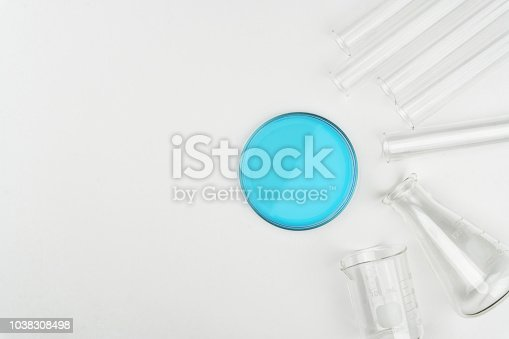 top view of laboratory equipments. A blue liquid Petri dish, flask, test tubes and beaker on the white table