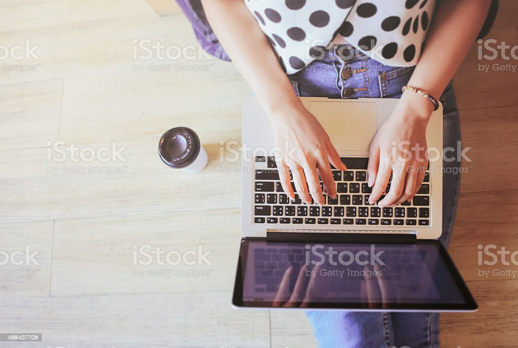 Top view of laptop in girl's hands sitting on floor stock photo