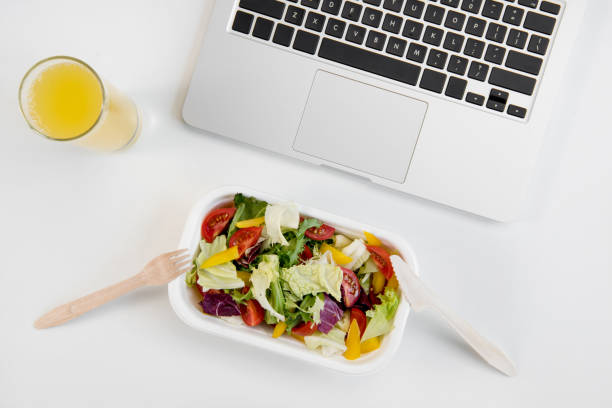 Top view of laptop, orange juice in glass and fresh salad in lunch box with plastic utensils at workplace stock photo