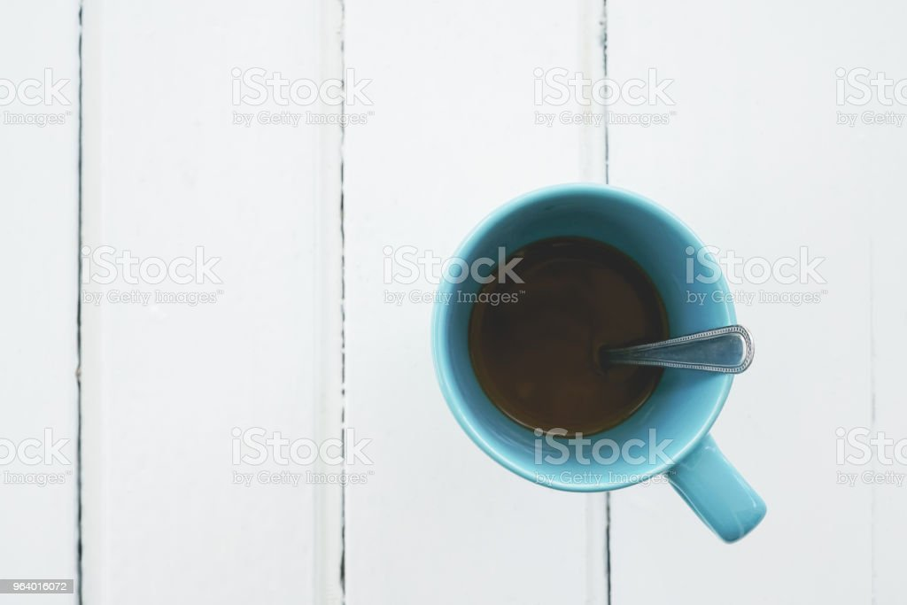 top view of leftover instant coffee in blue ceramic cup on white wooden desk - Royalty-free Blank Stock Photo