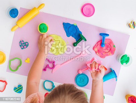 Top view of little girl toddler molding colorful clay on the table in the room