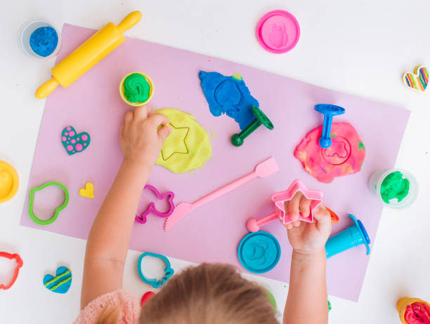 Top view of little girl toddler molding colorful clay Top view of little girl toddler molding colorful clay on the table in the room clay stock pictures, royalty-free photos & images