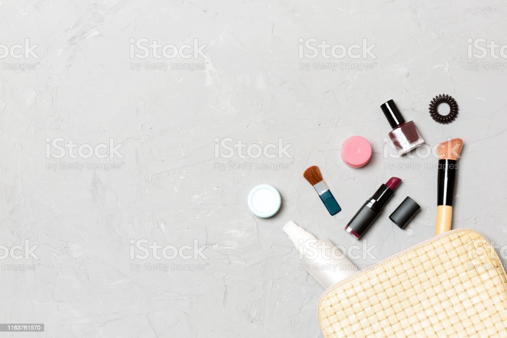 Top view of make up products fallen out of cosmetics bag on cement...