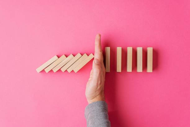 Top-Ansicht der männlichen Hand unterbricht kollabierende Dominos – Foto