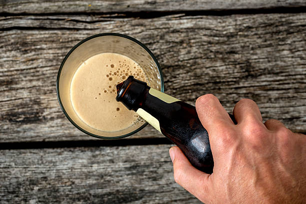 top view of male hand pouring dark beer in glass - dark beer stock photos and pictures