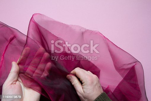 Top view of male hands holding purple tulle or organza on a pink background, selective focus